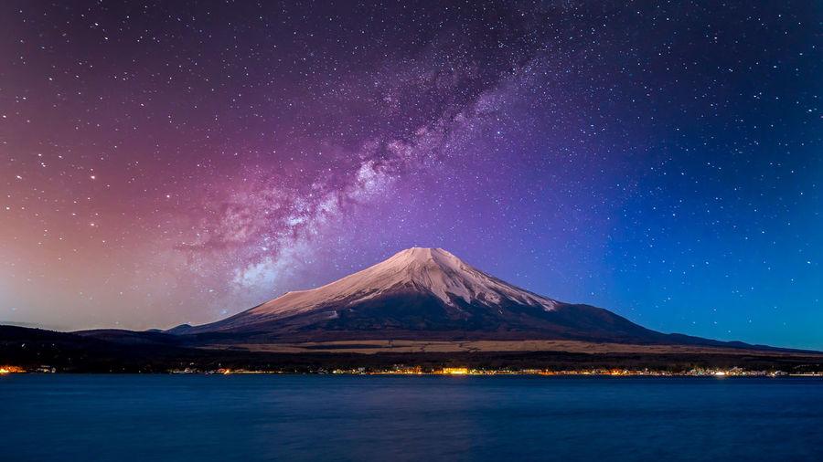 Fuji mountain at yamanachi in japan,  at night with milky way galaxy and kawaguchiko lake, japan.
