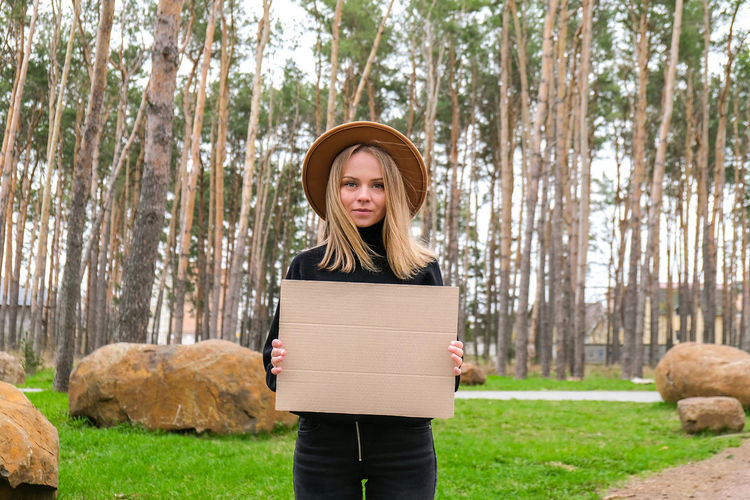 Portrait of caucasian young woman standing with cardboard outdoors. nature background. copy space