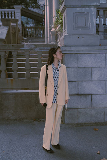 Full length of woman looking away while standing against building