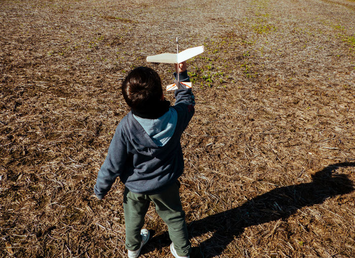 High angle view of boy playing with airplane model on land