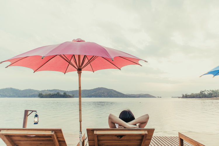 Woman sitting on deck chair by lake against sky