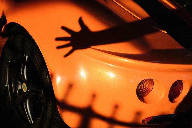 Close-up of orange shadow on black car
