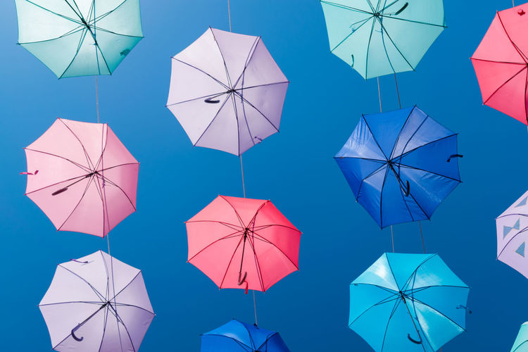 Low angle view of umbrellas against blue sky
