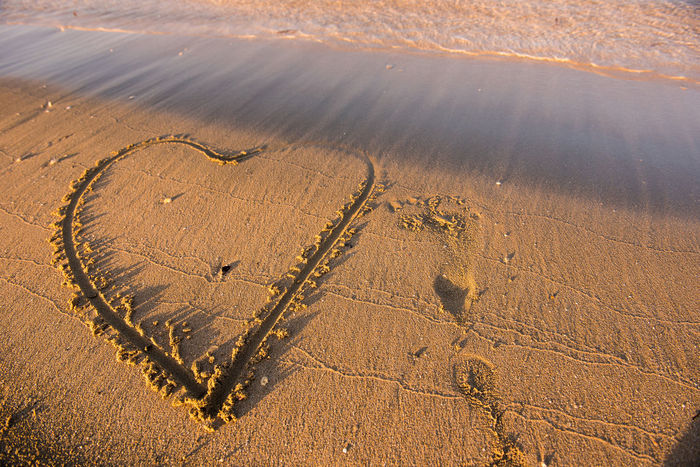 Heart drawn on sand. Waves approaching. Summer beach vacation concept Freedom Holiday Love Text Word Abstract Background Beach Character Day Destination Drawn Heart Letter Lettering Message Nature No People Ocean Outdoors Pattern Sand Sea Summer Written