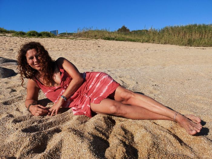 Portrait of woman relaxing at beach against clear sky