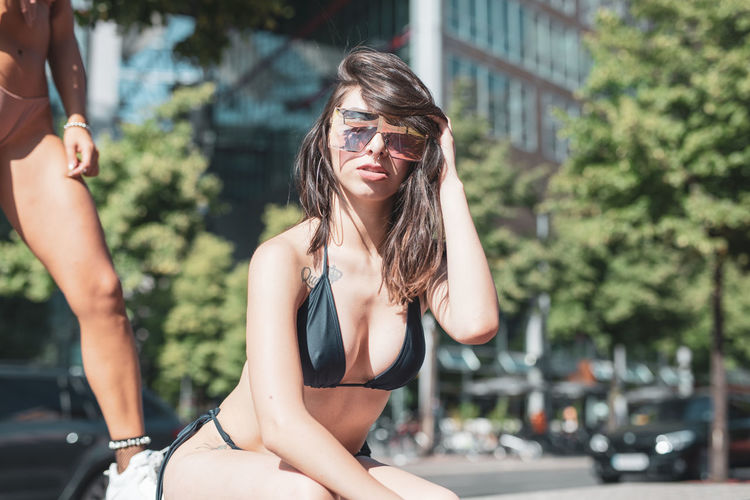Portrait of young woman wearing sunglasses and bikini in city during sunny day