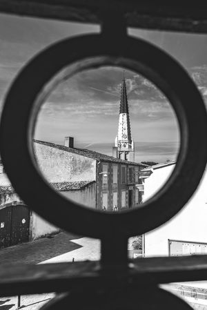The Church steeple in Ars en re through round ornamentic element. Monochrome photography. The Church Steeple Architecture Building Building Exterior Built Structure Circle City Day Design Focus On Background France 🇫🇷 Geometric Shape Monochrome monochrome photography Nature No People Ornamentic Element Outdoors Reflection Shape Sky Tall - High Tower Water Window 10