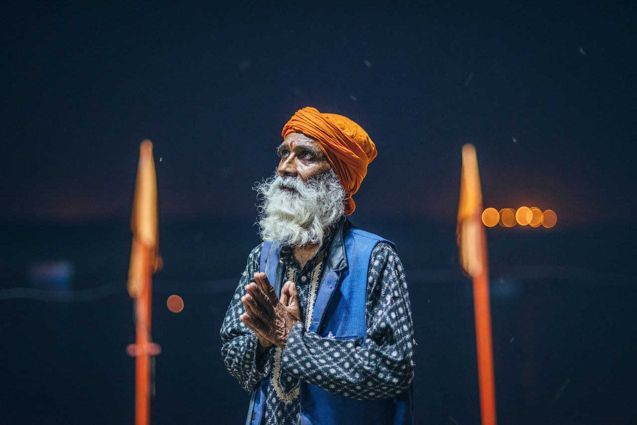 real people, one person, waist up, senior adult, front view, outdoors, holding, standing, focus on foreground, casual clothing, senior men, night, burning, leisure activity, beard, illuminated, lifestyles, flame, studio shot, gray hair, eyeglasses, warm clothing, close-up, people