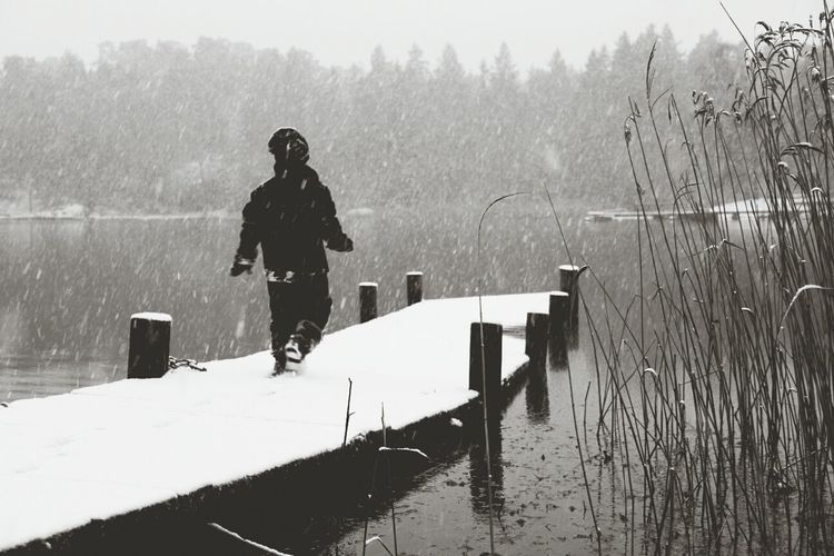 Child walking along jetty during winter