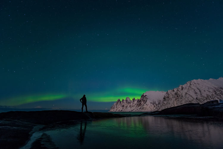 Rear view of man standing against aurora borealis at night