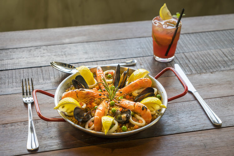 High Angle View Of Paella Served In Bowl With Drink On Wooden Table