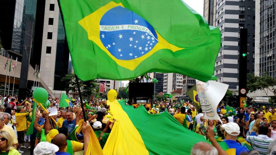 People enjoying with brazilian flag during festival in city