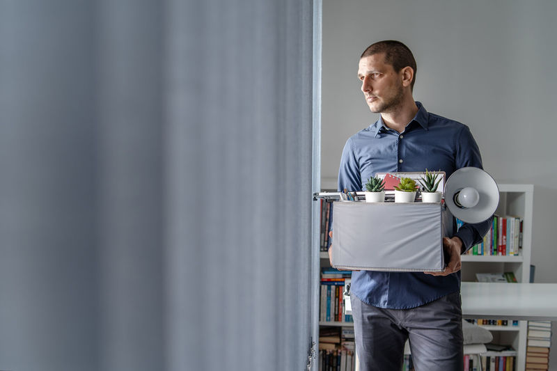 Businessman holding cardboard box looking away in office