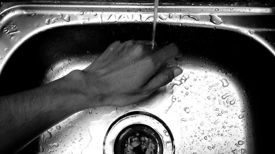 Cropped image of hand against water at home