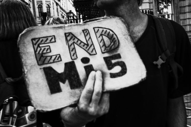 """A man holds an """"End MI5"""" banner outside the entrance to 10 Downing Street, London, UK Freedom Liberty London MI5 Protest Banner Close-up Communication Freedom Of Speech Holding One Person Outdoors Real People Text Uk"""