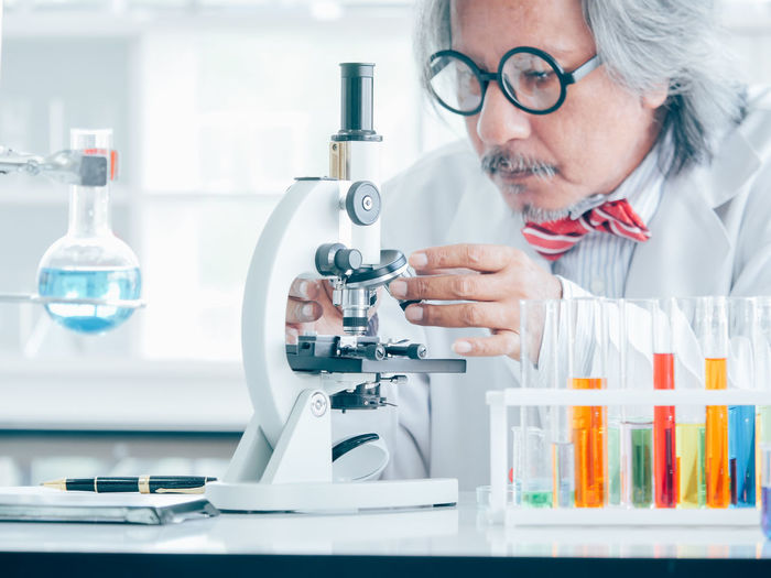 Healthcare And Medicine Science Education One Person Concentration Research Scientist Expertise Eyeglasses  Portrait Laboratory Equipment Indoors  Adult Laboratory Lab Coat Looking Occupation Headshot Microscope Mature Adult Scientific Experiment Analyzing Mature Men