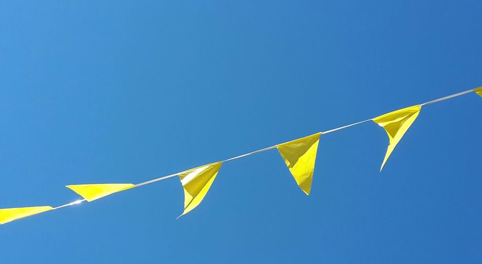LOW ANGLE VIEW OF FLAGS HANGING IN ROW AGAINST CLEAR BLUE SKY