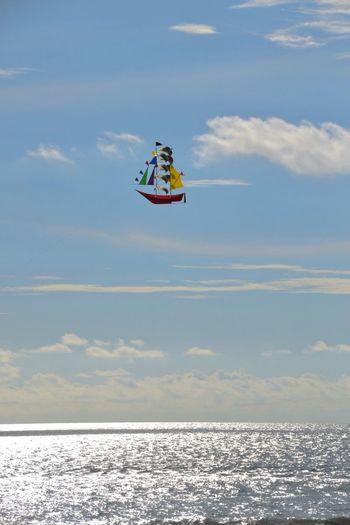 Boat Shaped Kite Flying Over Sea Against Sky