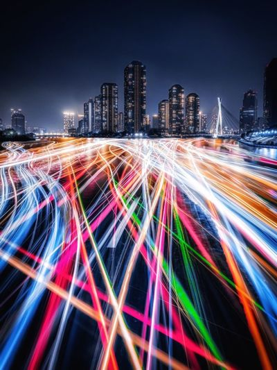 Light trails on street by illuminated buildings against sky at night