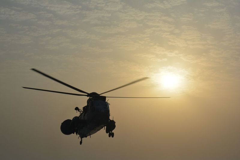 Low angle view of helicopter against sunset