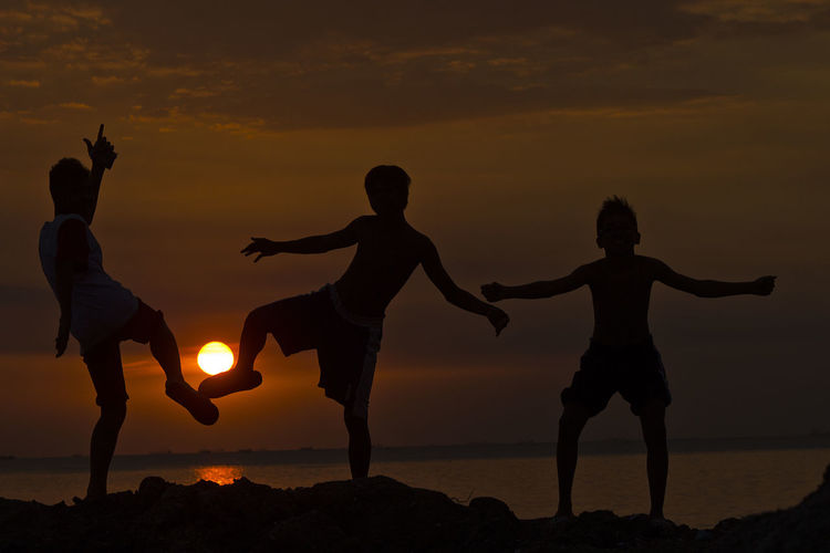 Silhouette Boys Enjoying On Rock Formation Against Sunset Sky