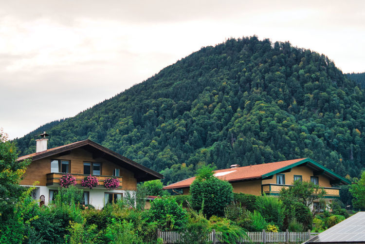 House amidst trees and mountains against sky