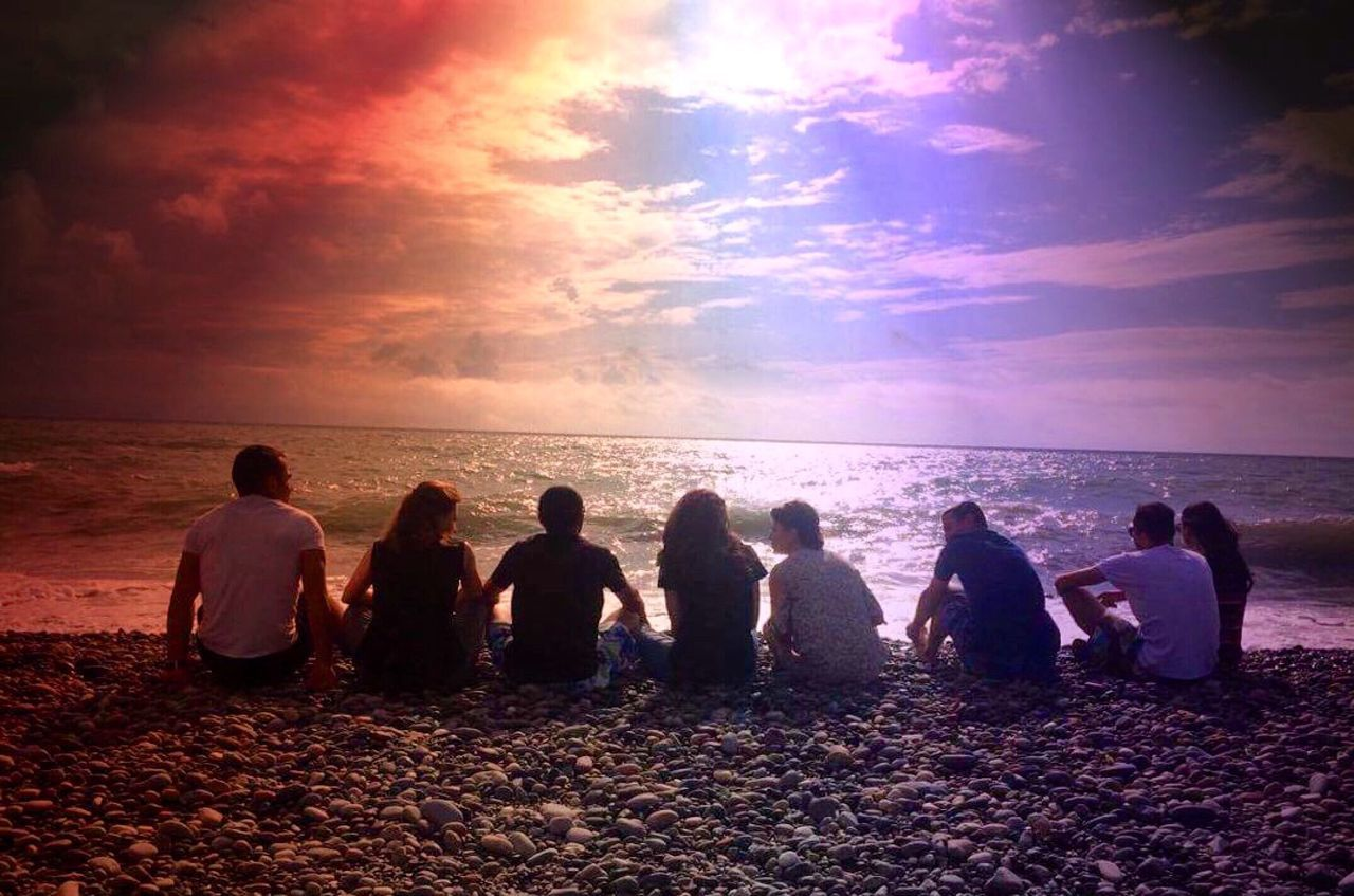 sea, beach, horizon over water, large group of people, sunset, water, sitting, sand, outdoors, men, relaxation, sky, women, togetherness, adult, nature, day, people, adults only