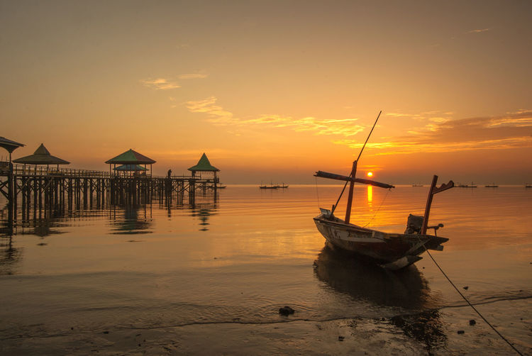 sailboat, sunrise Water Sky Sunset Nautical Vessel Transportation Sea Mode Of Transportation Scenics - Nature Orange Color Nature Tranquil Scene Beauty In Nature Tranquility Moored Beach Reflection No People Land Cloud - Sky Outdoors Sailboat Fishing Boat