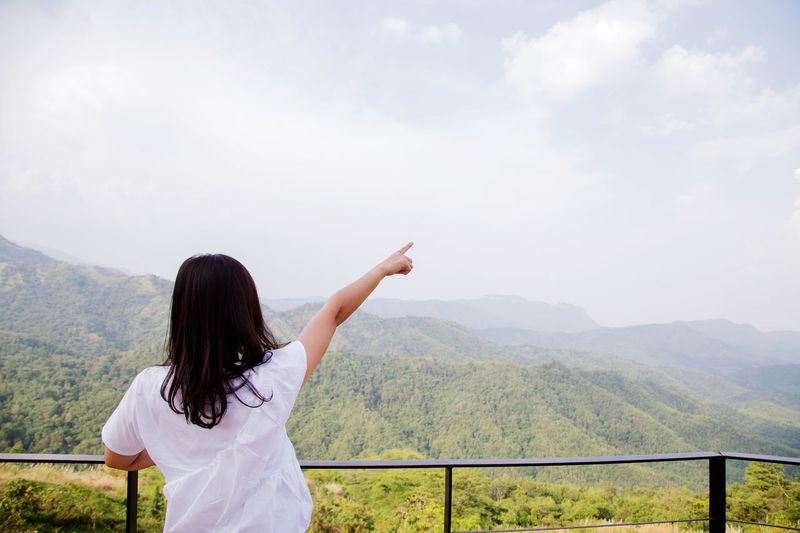 Rear view of woman with arms raised against mountain range