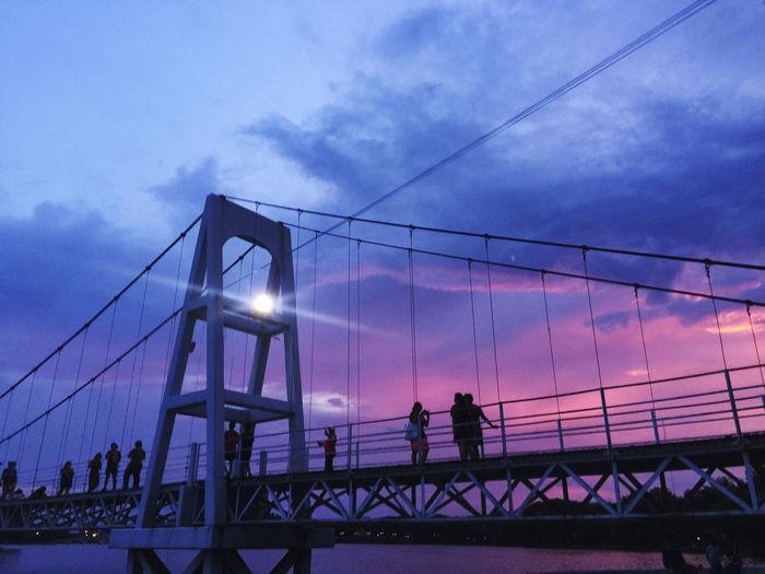 People walking on bridge against sky