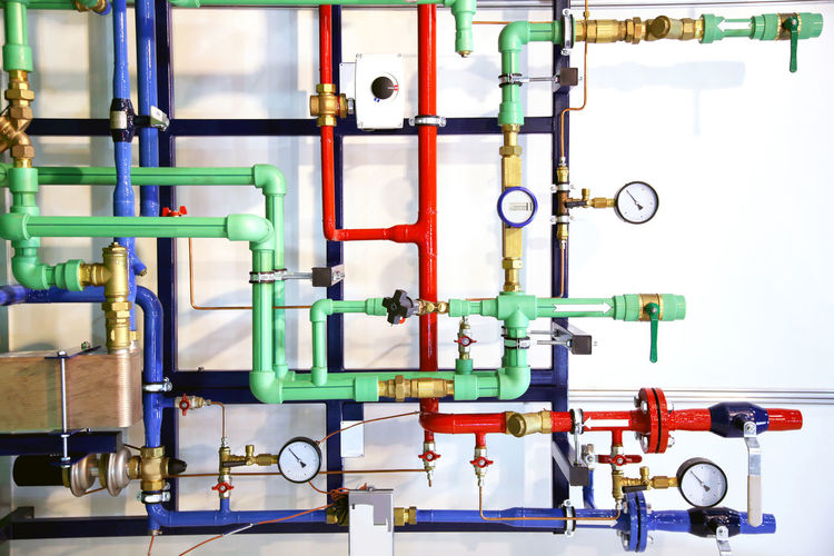 Colorful metallic pipes with gauge against wall