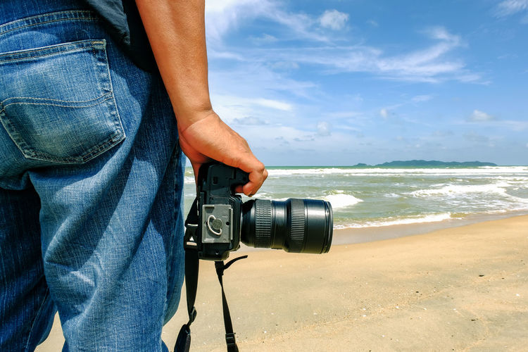 Man holding camera on beach