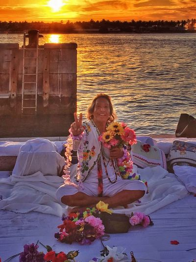 Peace and Love. ✌🏻❤️💐 Sunset Love Smiling Sitting Happiness Leisure Activity Real People Lifestyles Flower Outdoors Beauty In Nature Bonding Peace Peace And Love ✌❤ Peace Sign  Love Mallory Square Key West