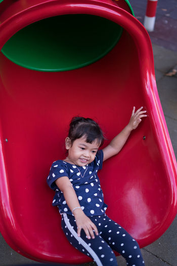 High angle view of happy girl sliding in playground