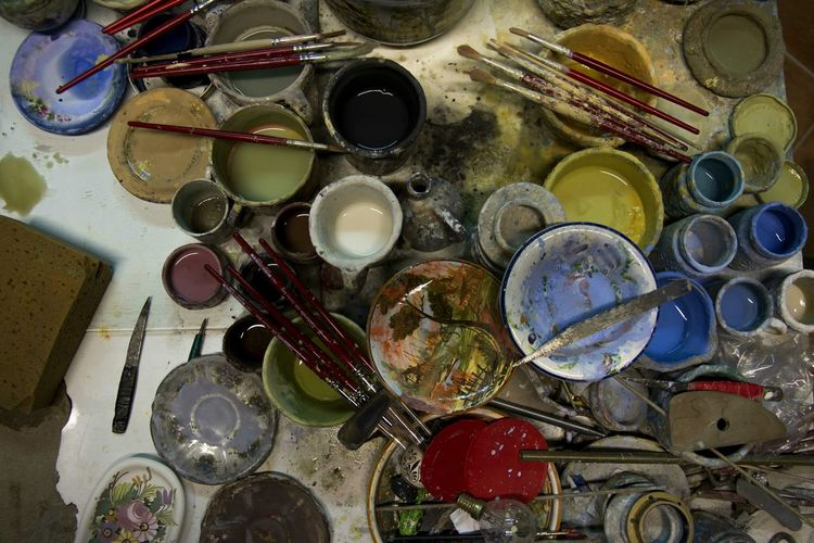 High Angle View Of Paintbrushes And Cans On Table