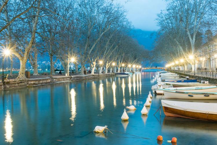Boats moored in lake at dusk
