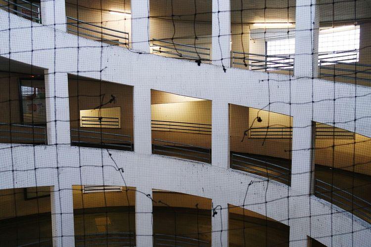 Parking lot building seen through broken net