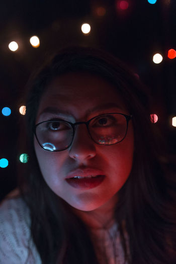 Close-up of young woman against illuminated lights at home