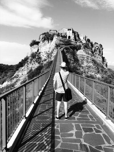Rear view of teenage boy standing on footbridge