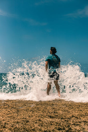 Full length of man splashing water on beach