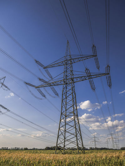 Low angle view of electricity pylon on land against sky