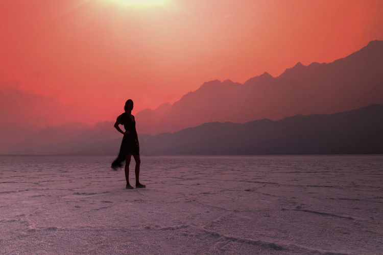 Silhouette man standing on mountain against sky during sunset