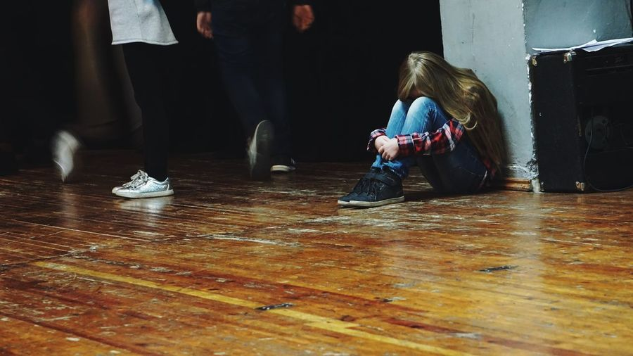 Low section of people walking by sad girl sitting on floor
