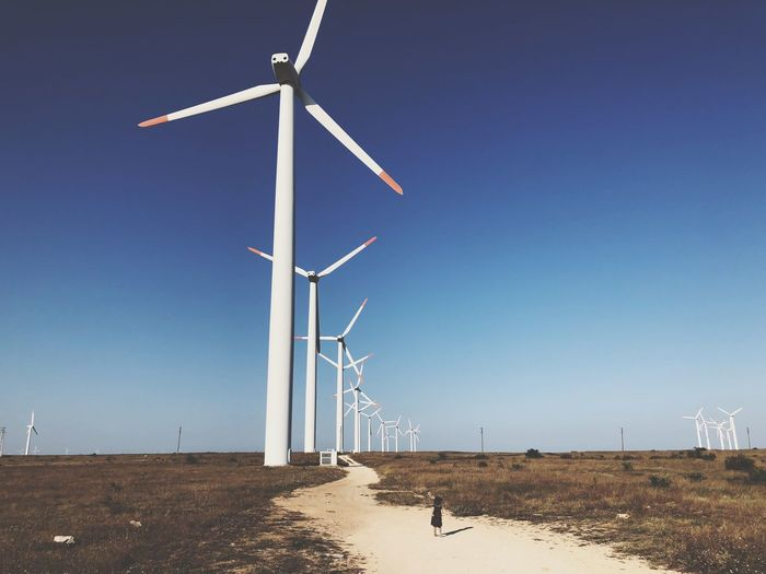 Girl Children EyeEm Selects Wind Turbine Turbine Alternative Energy Fuel And Power Generation Wind Power Renewable Energy Sky Technology Nature Environment Environmental Conservation Clear Sky Land Field Day Electricity  Rural Scene Landscape Blue