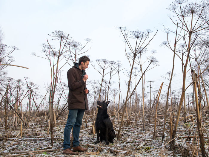 Man with dog standing on land during winter
