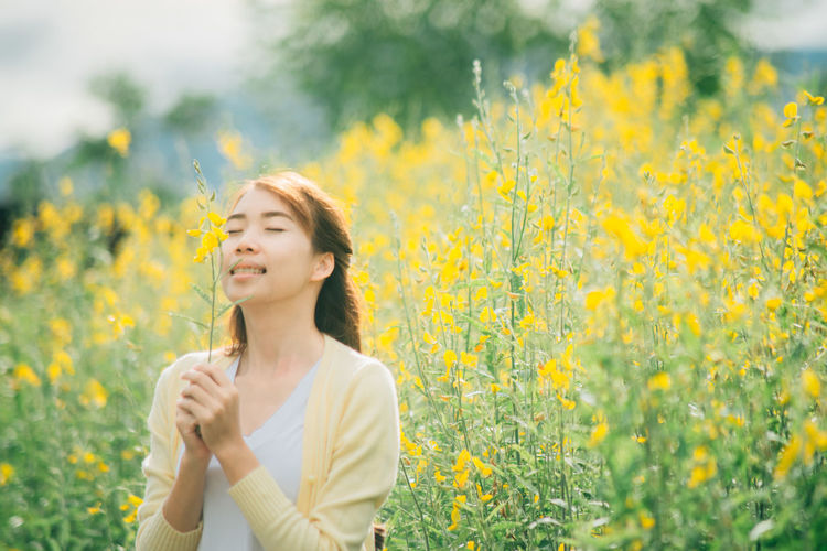 Young Woman Smelling Yellow Flower