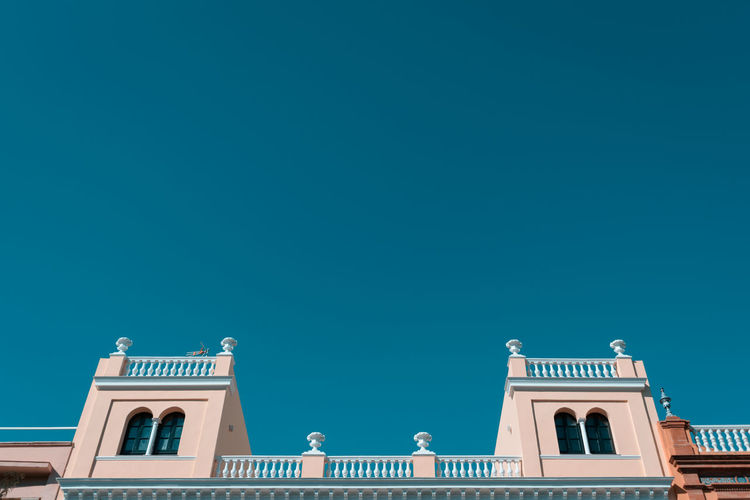 Upper section of a building in Sevilla, Spain shot from a public pavement Summertime Travel Architecture Blue Building Exterior Built Structure Clear Sky Copy Space Day Low Angle View negative space Outdoors Sky Split Tone Summer Travel Destinations Window