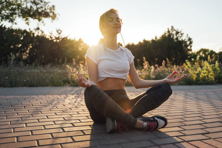 Young woman meditating on footpath during sunset
