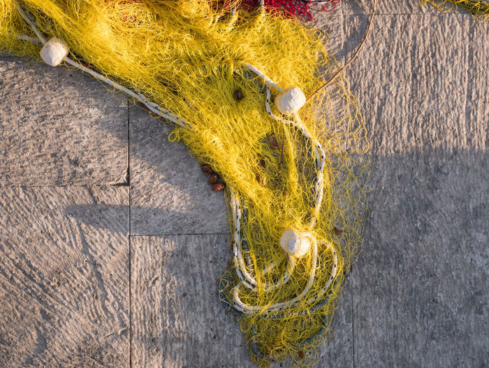 Colorful fishing net on stone shore top view Fishing Net Net No People Yellow Textile Close-up Material Day Outdoors Fishing Equipment Mediterranean  Dalmatia Croatia Object Industry Backgrounds Texture Travel Rope