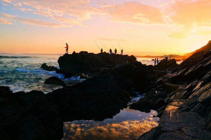 Friends fishing while standing on top of rock by sea during sunset